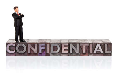 Hand painted businessman figurine and the word Confidential  in old metal letterpress isolated on a white background. Stock Photo - 18453494