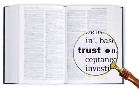 definitions: A magnifying glass held over a dictionary looking at the word TRUST enlarged Stock Photo