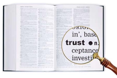 Een vergrootglas gehouden over een woordenboek te kijken naar het woord TRUST vergroot Stockfoto