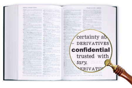 A magnifying glass held over a dictionary looking at the word Confidential enlarged photo