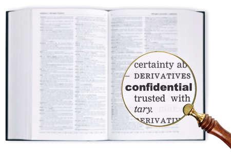 enlarged: Una lente di ingrandimento poggiata su un dizionario guardando la parola Confidential allargata