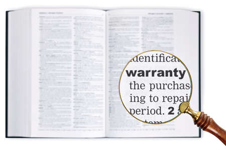 A magnifying glass held over a dictionary looking at the word Warranty enlarged photo