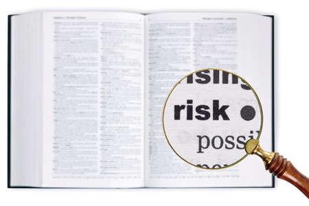 enlarged: Una lente di ingrandimento poggiata su un dizionario guardando la parola rischio ampliato Archivio Fotografico