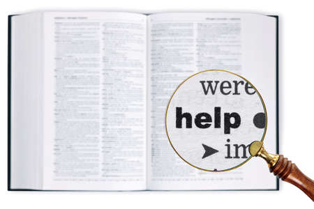 enlarged: Una lente di ingrandimento poggiata su un dizionario guardando la parola Aiuto allargata