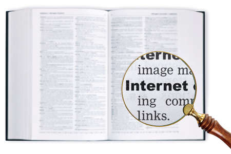 A magnifying glass held over a dictionary looking at the word Internet enlarged photo