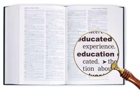 enlarged: Una lente di ingrandimento poggiata su un dizionario guardando alla parola educazione ampliato