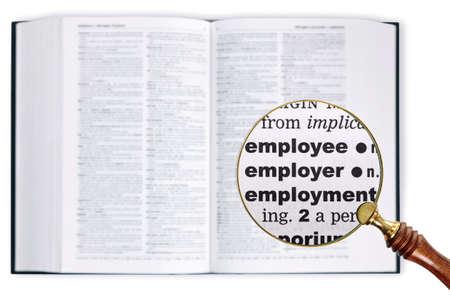 enlarged: Una lente di ingrandimento poggiata su un dizionario guardando le parole dei dipendenti, datori di lavoro e occupazione allargata Archivio Fotografico