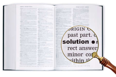 A magnifying glass held over a dictionary looking at the word Solution enlarged photo