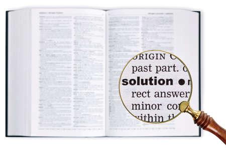 enlarged: Una lente di ingrandimento poggiata su un dizionario guardando la parola Solution ampliato