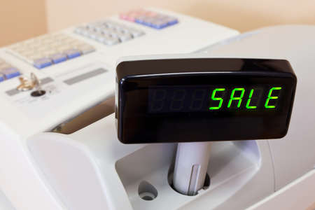 checkout counter: The word SALE on the display of a cash register