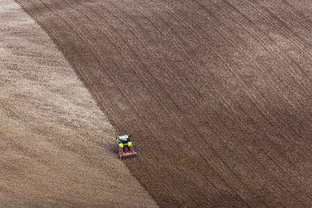 plough land: A tractor raking a ploughed field in preperation for sowing the years crop.