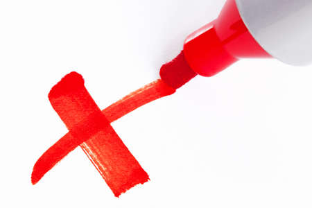 Close-up photo of a big red felt tip marker pen writing a cross X on white paper Standard-Bild