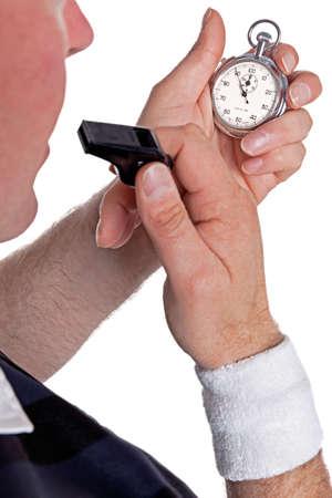 arbitros: Un árbitro que controla su cronómetro y punto de sonar el silbato, aislado en un fondo blanco.