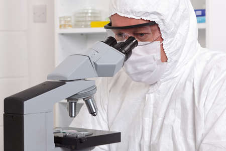 eyepiece: A male lab technician in sterile clothing looking through the eyepiece of a microscope. Stock Photo