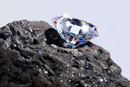 kohle: Foto von einem einzigen Diamanten auf einem St�ck Kohle vor einem einfarbigen Hintergrund.
