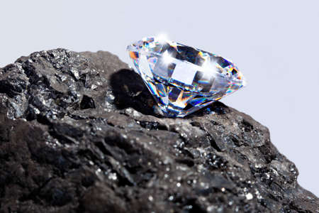 Photo of a single cut diamond on a piece of coal against a plain background. photo