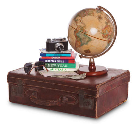 guides: Still-life photo of an old brown leather suitcase with camera, travel guides, world globe, sunglasses, stamped passport and money. Isolated on a white background with clipping path.