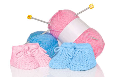 booties: Knitted baby booties with blue and pink wool plus knitting needles, isolated on a white background.