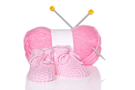 Baby girl knitted booties with pink wool and knitting needles, isolated on a white background. photo