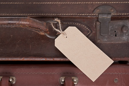 Photo of a blank baggage label on an old brown leather suitcase