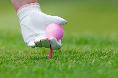 A ladies hand in white leather glove holding a pink golf ball placing a tee into the ground