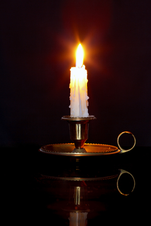 A single burning candle in a brass holder known as a chamberstick, against a black background.