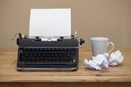 An old retro typewriter with a piece of blank paper for you to add your own text, coffee mug and two pieces of screwed up paper besides it on the desk. Stock Photo