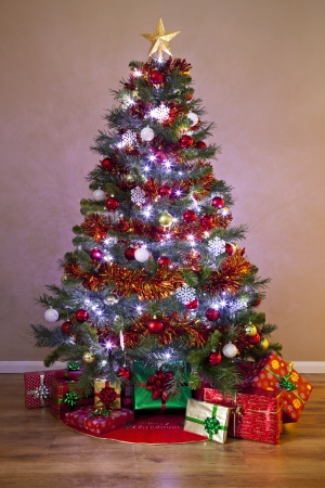 a decorated christmas tree in a home lit up with fairy lights and surrounded by - Light Up Presents Christmas Decorations