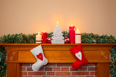 Christmas stockings hanging over a fireplace with candles on the mantlepiece Stock Photo