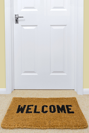A Welcome doormat in front of a door. Imagens