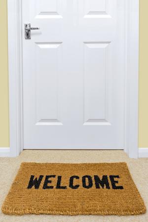 Een Welkom deurmat voor een deur.
