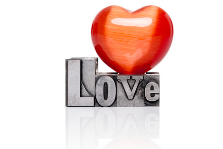 Love in old mixed font metal letterpress blocks with a red gemstone heart on top, isolated on a white . Stock Photo - 25236768