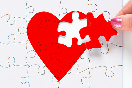 A woman putting the missing piece of a jigsaw red heart in place, good image to represent a love, broken heart, heartbreak, romance or Valentines theme.