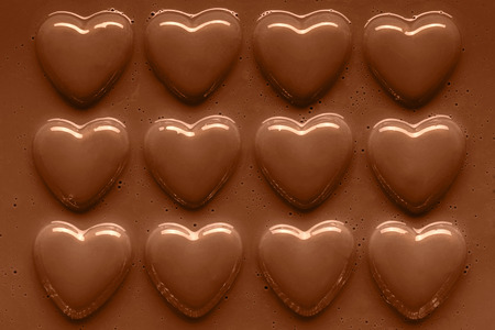 chocolate hearts in a row smothered in smooth melted milk chocolate