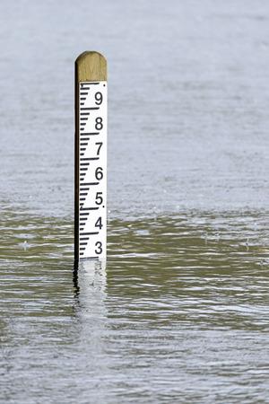 niveau d'inondation poste de marqueur de profondeur avec la pluie qui tombe dans l'eau environnante