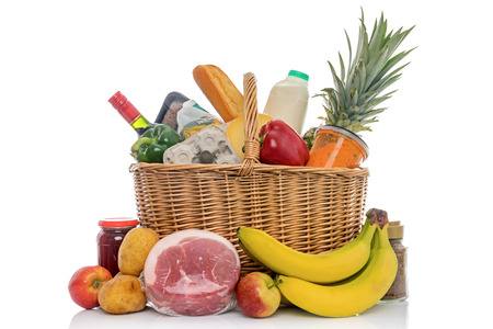 Wicker shopping basket full of groceries including fresh fruit, vegetables, meat and dairy products. Isolated on a white background. Stock Photo