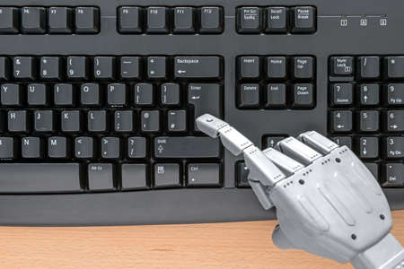 web robot: Robot hand typing on a computer keyboard. Stock Photo