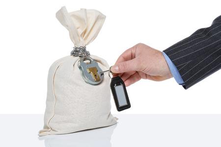 Businessman unlocking a money sack, white background, blank tag on key fob. Standard-Bild