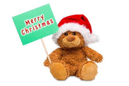 A teddy bear wearing a Santa hat holding a sign with Merry Christmas written on it, isolated on a white background.