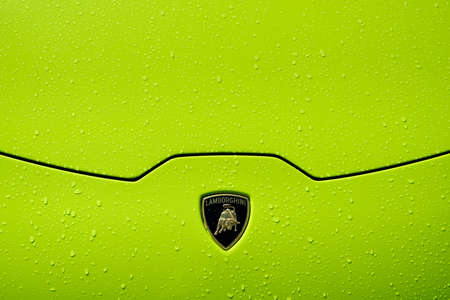 Lamborghini Huracán LP 610-4 bonnet detail with badge, lime green paintwork and raindrops.
