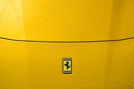 Ferrari F12 bonnet detail with badge, yellow paintwork and raindrops.