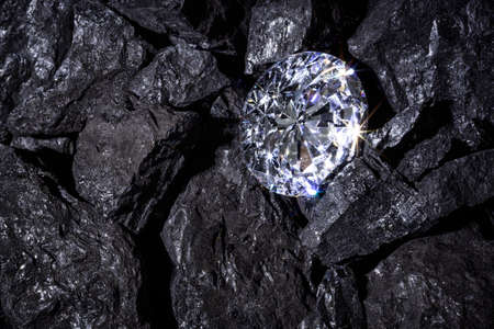 A single solitaire Diamond in amongst some pieces of coal.  Reklamní fotografie