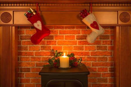 Two Christmas stocking hanging over a fireplace with gifts and a candle.