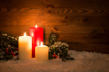 Christmas candles with Holly and conifer branches on an artificial snow and wooden background. Standard-Bild