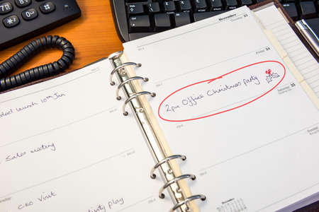 A desk diary with an entry for the office Christmas party circled in red. Standard-Bild