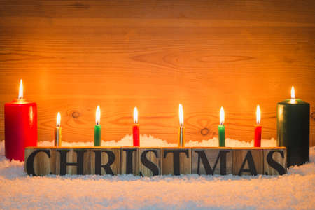 Christmas made from wooden letters in snow with candles background. Standard-Bild