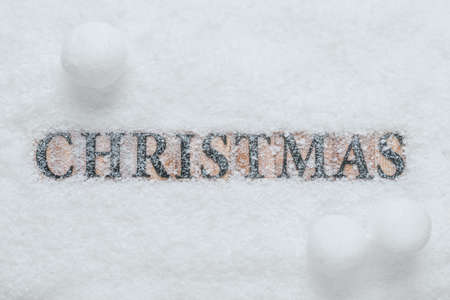 The word Christmas made with wooden letter blocks, on a snow background with snowballs. Standard-Bild
