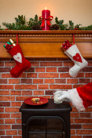 Stockings hanging over a fireplace at Christmas Eve with Santa taking a glass of milk thats been left out for him.