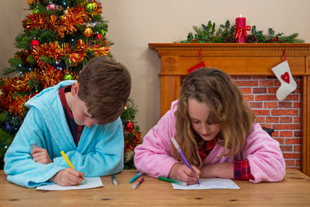 Two children, a boy and a girl, writing their Christmas letters to Santa