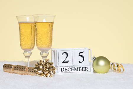 Christmas party still life with two glasses of Champagne and a date block showing 25th December. Copy space on the background for your own message such as invitation. Standard-Bild